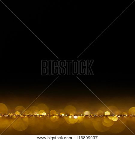 Gold Festive Christmas background. Abstract twinkled bright background with bokeh defocused golden lights