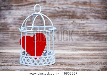 Heart In Cage With Wooden Background