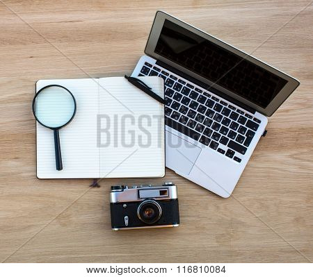 Notebook, notepad with pen, magnifier and camera - laid out on a wooden table, top view.