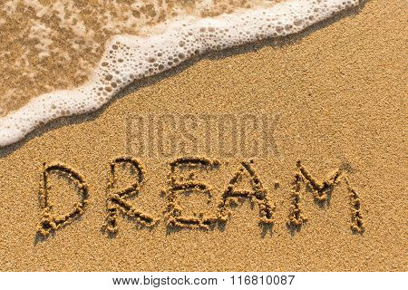 Dream - word drawn on the sand beach with the soft wave.