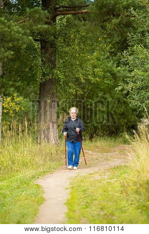 An elderly woman on a walk in the Park practicing Nordic walking.