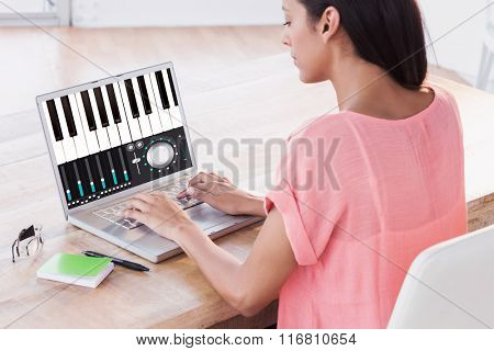 Businesswoman using laptop at desk in creative office against music app