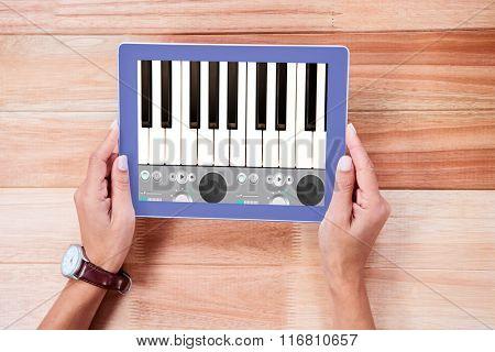 Music app against overhead of feminine hands using tablet