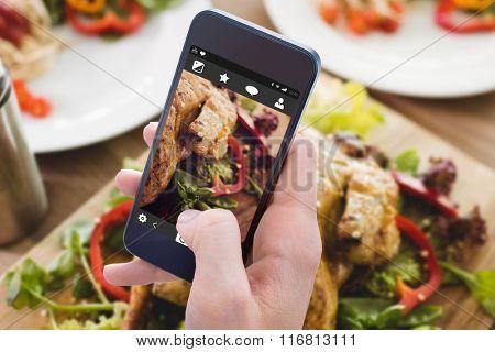 Woman using her mobile phone against healthy food prepared