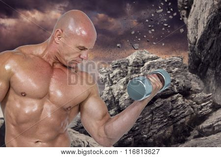 Bodybuilder concentrating while lifting dumbbells against rock crashing down from cliff
