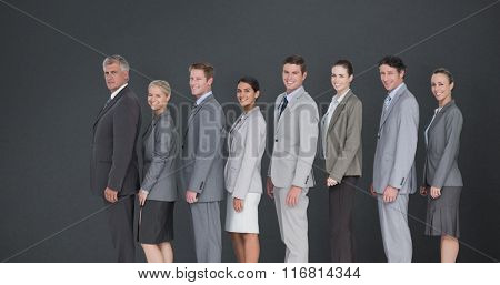 Business team standing in row and smiling at camera against grey background