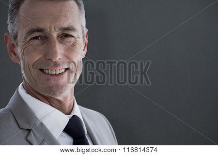 Close-up portrait of confident businessman smiling against grey background
