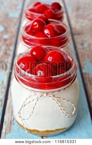 Row of cherry cheesecakes in mason jars