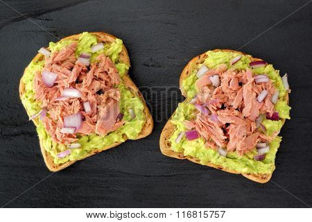 Open avocado sandwiches with tuna against dark slate