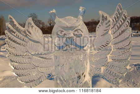 Ice figure of an owl in the park in winter on a clear day