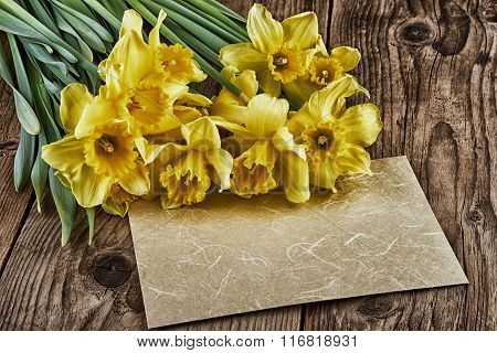 Vintage Still Life with Yellow Daffodils and Paper Sheet on Old Wooden Board