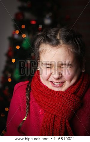 Little Girl With Pigtails In Red Knitted Sweater Against The Backdrop Of The Christmas Tree, Dark Ba
