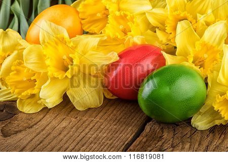 Yellow flowers with Easter eggs closeup