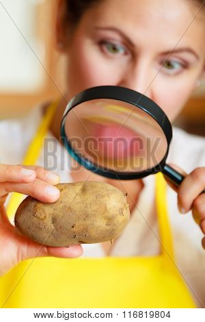 Woman Inspecting Potato With Magnifying Glass.
