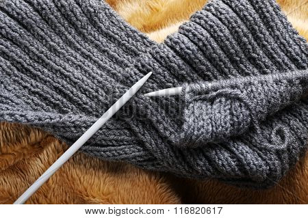 Close Up Of Knitted Scarf With Kntting Needles.