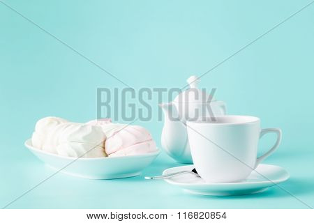 Delicate Meringues, Marshmallows And Cup Of English Tea On White Table