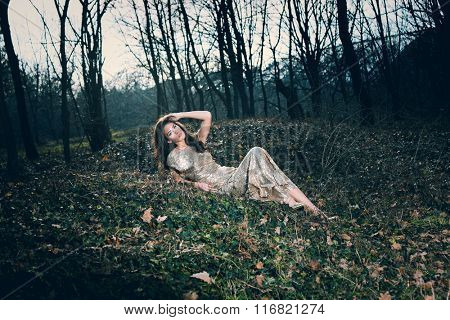 beautiful young woman in elegant glittering  dress  in wood lie on leaves full body shot