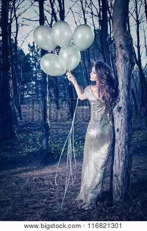 beautiful young woman in long elegant glittering  dress with balloons  in wood full body shot