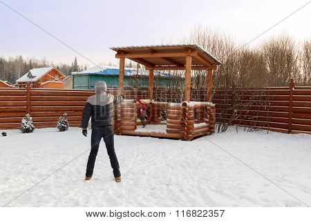 Father Plays With Child Snowballs In Backyard