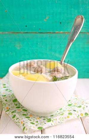 Soup With Potatoes, Rice And Meatballs In A White Cup On A Bright Background
