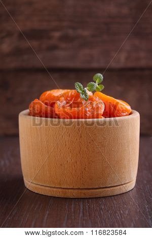 Dried Apricots In A Wooden Bowl With Mint Leaf