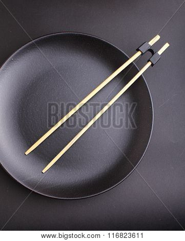 Round Black Plate With Chopsticks For Sushi On A Black Background