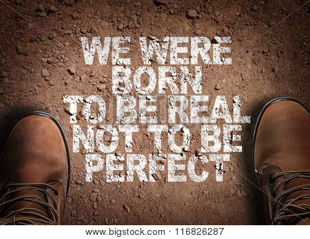 Top View of Boot on the trail with the text: We Were Born To Be Real Not To Be Perfect