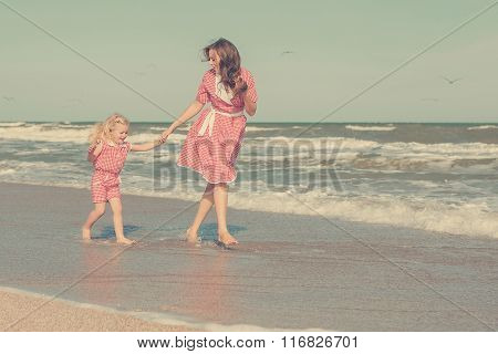 Mother And Her Daughter  Having Fun On The Beach