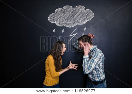 Crazy young couple standing under drawn raincloud and yelling on each other over blackboard background