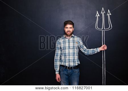 Smiling bearded young man standing and holding drawing trident over chalkboard background