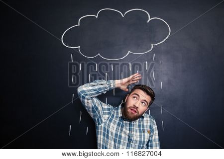 Unhappy young man hiding from raincloud and rain drawn over him on a blackboard background