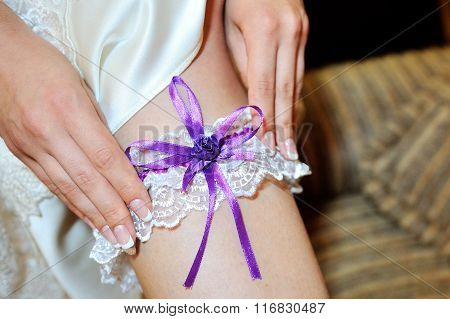 Bride Dresses Garter On The Leg