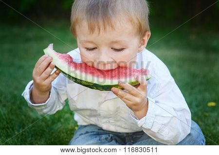 Little Boy Eating Watermelon In The Summer Garden
