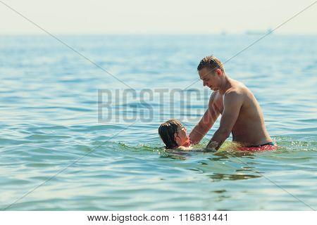 Little Girl Kid And Man Father In Sea Water. Fun