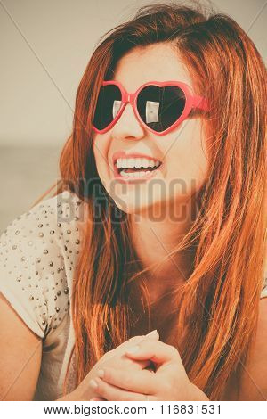 redhaired happy girl in heart shaped sunglasses