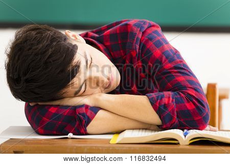 Male Student Sleeps On The Desk In Classroom