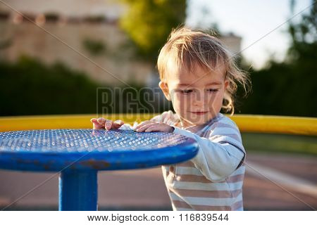Baby boy child plays in playground area