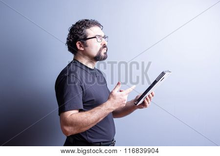 Thoughtful Man Holding Tablet And Counting On Hand