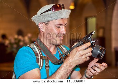 Young man tourist with backpack takes a photo shot