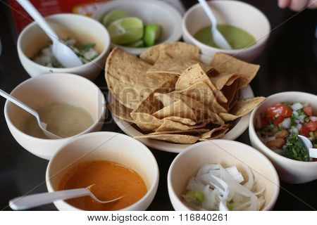 Mexican tortilla chips surrounded by bowls of salsa/other sauces.