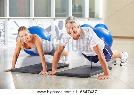 Man and woman doing push ups together in a gym