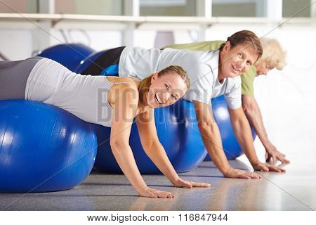 Happy senior group doing back training in health club on gym ball