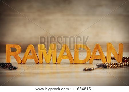 Ramadan word with wooden letters and rosary on table
