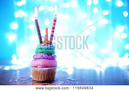 Cupcake with varicolored cream icing and candles on a glitter background