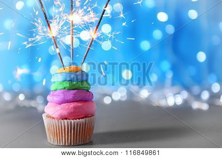 Cupcake with varicolored cream icing and sparklers on a glitter background, close up