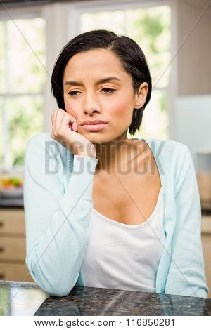 Upset brunette with hand on chin sitting in the kitchen