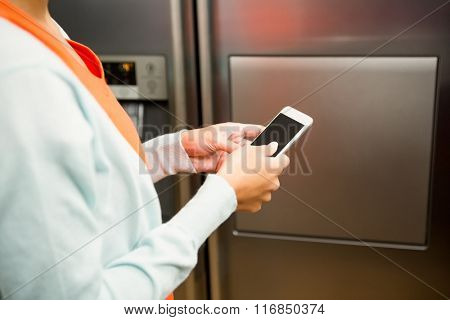 Close up of woman using smartphone near the refrigerator in the kitchen