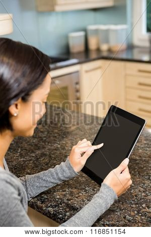 Brunette using tablet with black screen in the kitchen