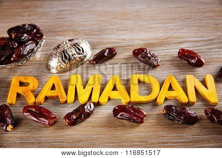 Ramadan word with wooden letters and dry dates on table