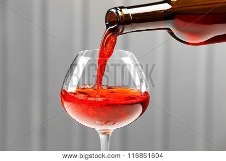 Pouring wine on wall background
